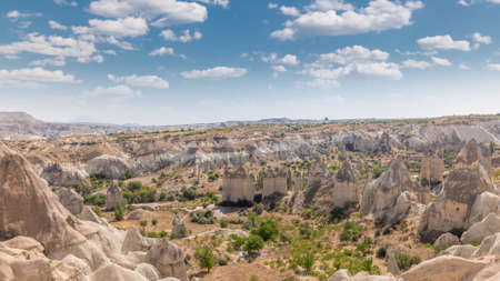 Red Valley and Rose Valley of Goreme of Nevsehir in Cappadocia aerial timelapse, Turkey. Love valley and fairy chimneys panoramic view with clouds on a blue sky