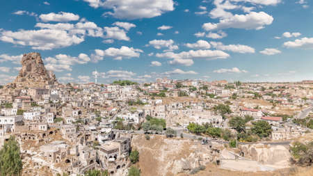 View of Ortahisar town old houses in rock formations from Ortahisar Castle aerial timelapse. Cappadocia. Nevsehir Province. Turkey. Cloudy blue sky
