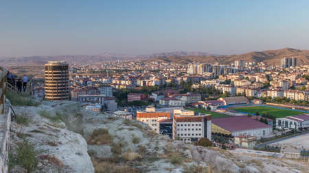 Aerial view from old castlethe in historical city town of Nevsehir timelapse. Panoramic skyline with buildngs covered by warm sunset light
