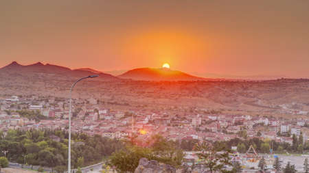 Sunset view from old castlethe in historical city town of Nevsehir aerial timelapse. Panoramic skyline with hills and park at evening Archivio Fotografico