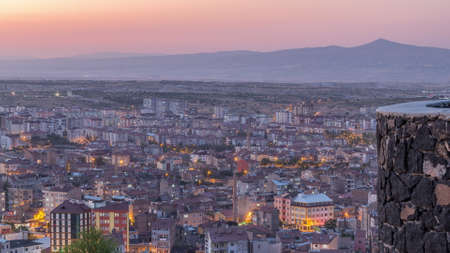 Aerial view from old castlethe in historical city town of Nevsehir day to night transition timelapse. Panoramic skyline with illuminated buildngs and roads after sunset Archivio Fotografico