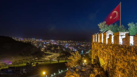 Aerial view from old the in historical city town of Nevsehir night timelapse. Panoramic skyline  illuminated flag and walls  lights