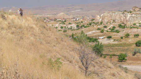 Red Valley and Rose Valley of Goreme of Nevsehir in Cappadocia aerial timelapse, Turkey. Love valley and fairy chimneys panoramic view with green trees