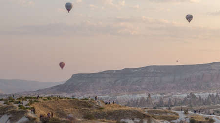 People watching a beautiful sunrise from viewpoint with colorful hot air balloons flying in clear morning sky above unusual rocky landscape aerial timelapse in Cappadocia, Turkey