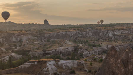 Colorful hot air balloons flying in clear morning sky with orange clouds above unusual rocky landscape aerial timelapse in Cappadocia, Turkey