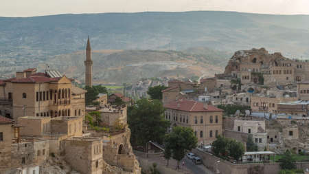 Urgup Town aerial view from Temenni Hill in Cappadocia Region of Turkey timelapse. Old houses and buildings in rocks at early morning with cars on a road Archivio Fotografico