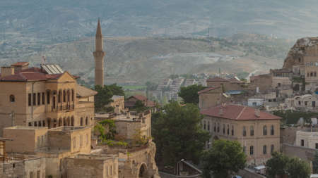 Urgup Town aerial view from Temenni Hill in Cappadocia Region of Turkey timelapse. Old houses and buildings in rocks at early morning with cars on a road Stock fotó