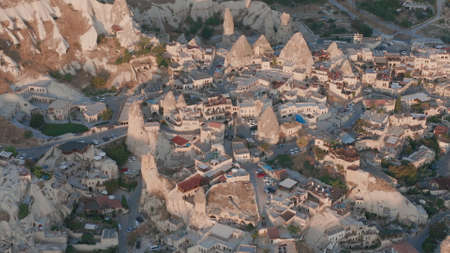 Aerial view from hot air balloon with houses and rocks during Sunrise over the fairytale landscape hills of Kapadokya with morning light. Goreme, Cappadocia, Turkey Archivio Fotografico