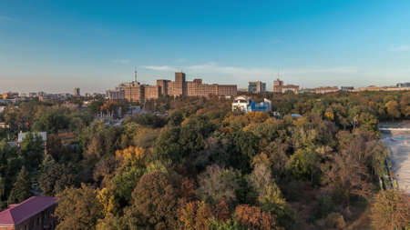 Aerial panoramic view to a staircase with fountains in the Shevchenko Garden timelapse. Park with yellow, red and green trees at autumn evening. Univercity building on a background. Kharkov, Ukraine