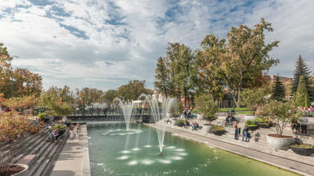 Lake with a fountains in the updated Shevchenko Garden in Kharkov panoramic timelapse. People walking around and sitting on benches