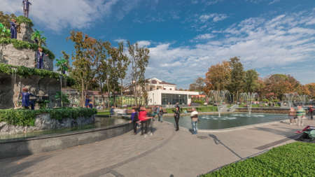 Lake with a fountains in the updated Shevchenko Garden inn Kharkov panoramic timelapse. People walking around and sitting on benches near fountain with monkeys