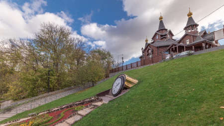 The temple in honor of the icon of the Mother of God Joy and Consolation and clock on flowerbed in Sarjin yar panoramic timelapse with playground in Kharkov, Ukraine Archivio Fotografico
