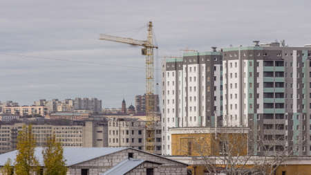 Crane and building construction site in a big city aerial timelapse during all day. Workers laying briks walls of new residential appartment house