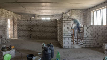 Builders laying brick walls inside appartment with professional tools timelapse. Workmen at work, bricklayers building wall, contractor and worker. Building materials around Archivio Fotografico