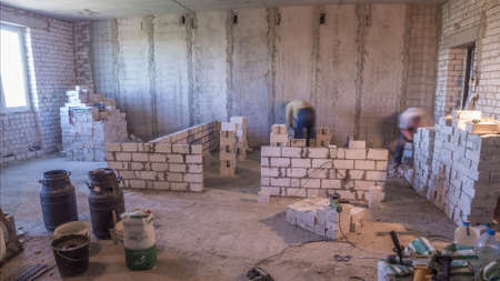 Builders laying brick walls inside appartment with professional tools timelapse. Workmen at work, bricklayers building wall, contractor and worker. Building materials around Stock fotó