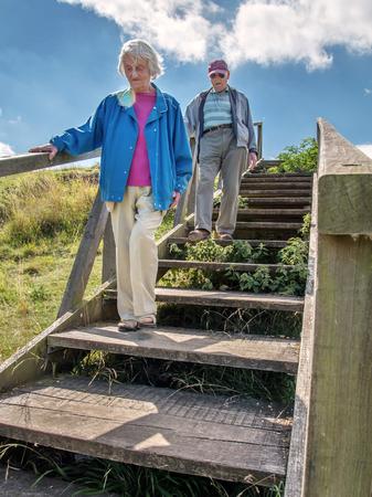 Un homme de 90 ans emmène sa femme, qui a une grave perte de vue, à Danebury Ring dans le Wiltshire pour la sortir dans la nature et loin des limites de son mode de vie confiné à la maison. Elle a une dégénérescence maculaire aiguë. Banque d'images