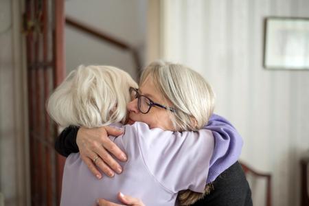 Mutter möchte nicht, dass ihre Tochter geht - Nach einem Besuch bei ihrer alten und sehbehinderten Mutter umarmt sich die Tochter und verabschiedet sich von ihrer Mutter, bevor sie lange nach Hause fährt.