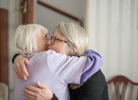 After a visit to see her elderly and sight impaired mother,the daughter hugs and says goodbye to her mom, before her long drive back home. Imagens