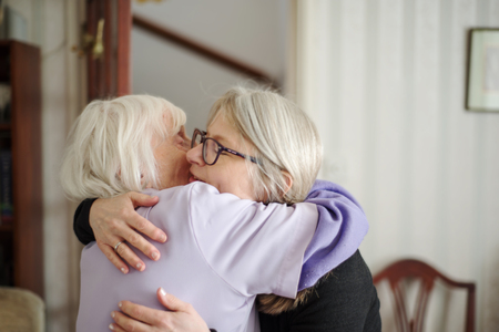 A sad goodbye-after a visit to see her elderly and sight impaired mother,the daughter hugs and says goodbye to her mom, before her long drive back home.