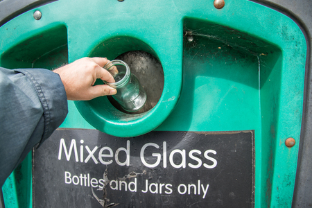 Putting glass bottles and jars into collection bin at local recycling center,Hampshire,UK.bottle bank. Reklamní fotografie