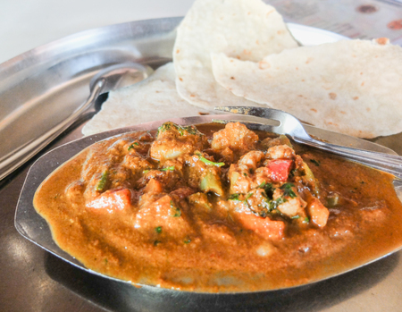 Very spicy Goan Indian curry served on a mtal plate and tray at a restaurant in Colva,India.