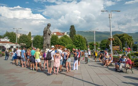 Guided tour group gathers around statue of St Clement ,near the harbour and lake.who founded the Monastery of St Clement in Ohrid
