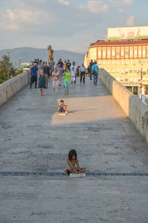 SKOPJE,NORTH MACEDONIA/AUGUST 22 2018:Young children sit on Stone Bridge asking for money from passers by.Skopje,2018.