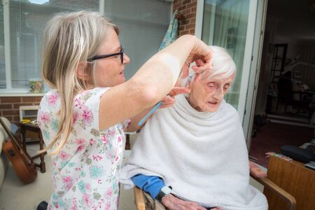 Covoid 19 restrictions means the old lady cannot be taken to the hair dresser as usual,so her visiting carer trims and combs her hair for her as it gets too long.