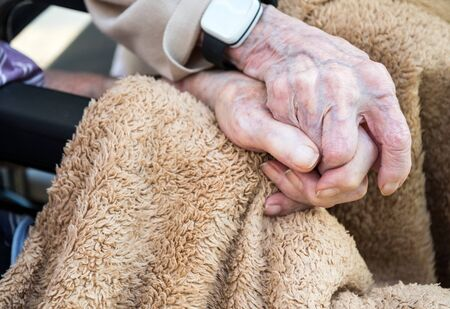 Husband and wife in their 90s still in love and the wife has early stage dementia.Natural and unposed in their back garden during springtime.
