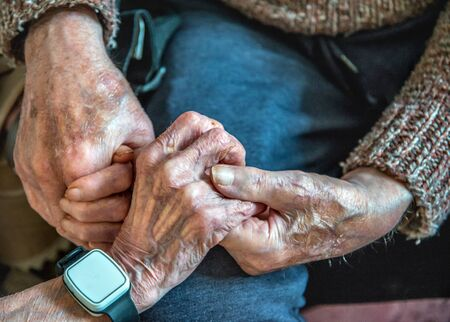 Clasping their old hands together,still in love in their 90's,together,both living and sleeping in the living room downstairs due to their ill health and looked after by family and carers.