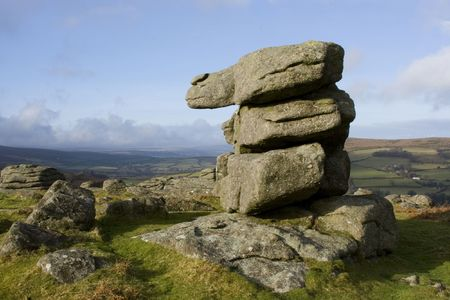 Pile of rocks formation in shape of number 1 one, with view over moors Dartmoor, Devon, England UK