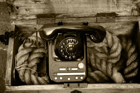 Sepia photo of phone in a wooden box of rope on sale on the market stall of the Braderie, Lille, France, 2007 photo
