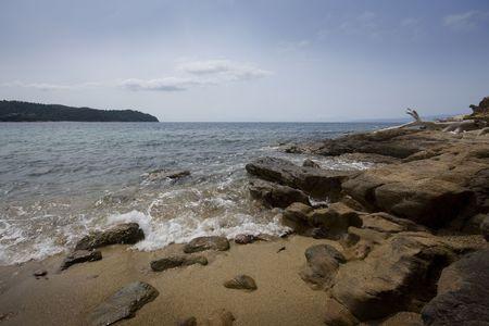 skiathos: Waves over rocks on Skiathos beach, Greece Stock Photo
