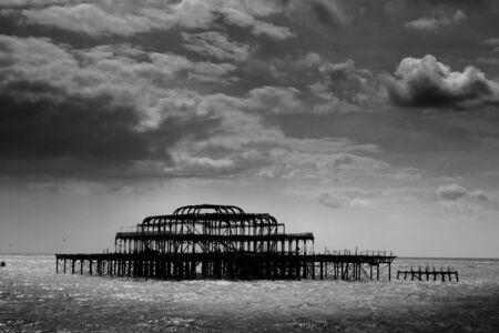 pier: Remains of Brighton Pier left standing in sea with dark clouds, Brighton West Pier, England, UK