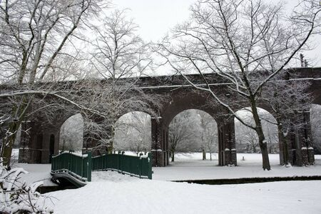 Early morning with snow covered London Underground bridge photo