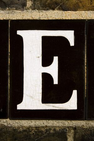 The letter E from tiled street sign on brick wall London England UK photo