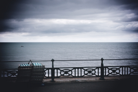 Deck chairs on seafront with stormclouds, Brighton