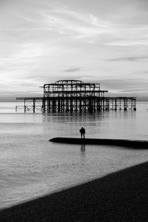 Couple infront of the remains of Brighton Pier left standing in sea at sunset Brighton West Pier England UK photo