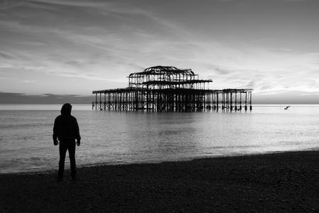 Remains of Brighton Pier left standing in sea at sunset Brighton West Pier England UK photo