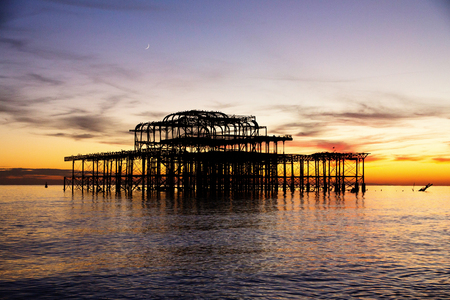 Remains of Brighton Pier left standing in sea at sunset Brighton West Pier England UK