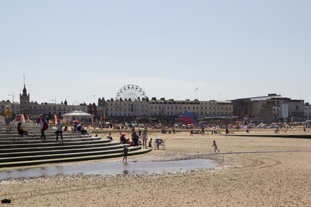 recently: MARGATE, KENT, UK - AUGUST 8. 2015. Margate beach with Dreamland amusement park in distance, originally opened 1880 recently restored, Margate, Kent, UK. Editorial