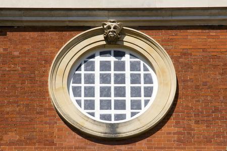 LONDON, UK - May 11, 2018. Round window at Hampton Court Palace which was originally built for Cardinal Thomas Wolsey 1515, later became King Henry VIII residence. London, Uk - May 11, 2018 Redakční