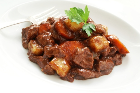 cubed: traditional beef stew with fork on white background