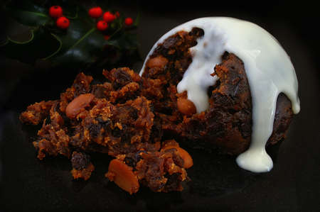 traditional English Christmas pudding with white sauce on black background