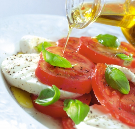 tomatoes and mozzarella with basil leaves and olive oil