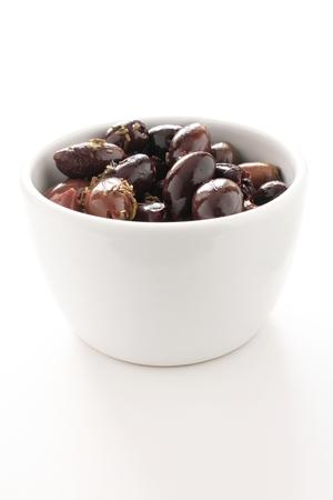 白い皿に緑と黒のオリーブ