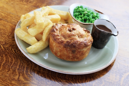 steak and mushroom pie with chips and peas Stock Photo