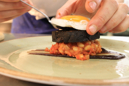 bacon baked beans: Bacon Egg Black Pudding Baked Beans Plated Meal Stock Photo