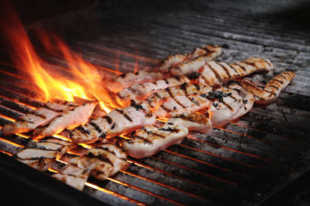 meat grill: chicken fillets cooking on flaming charcoal grill