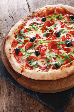 dinne: whole fresh baked pizza with olives and salami Stock Photo